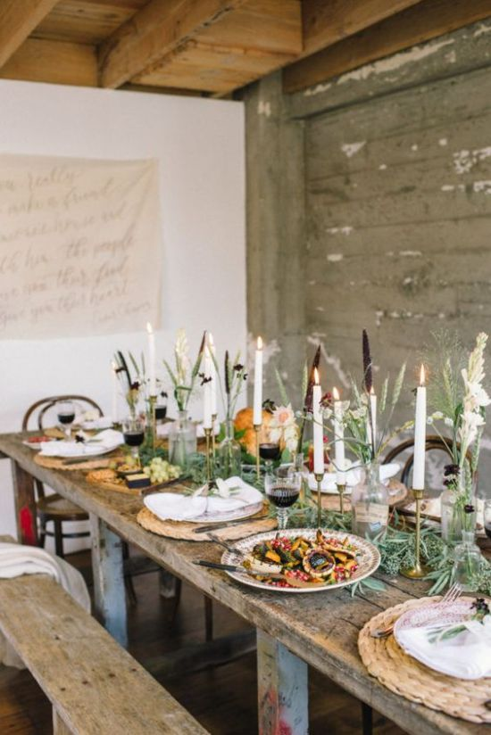 A Chic Thanksgiving Tablescape With Woven Placemats Tall Candles A Greenery Runner And Some Pumpkins