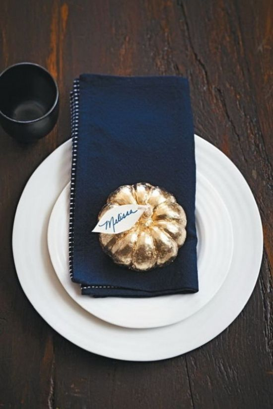 A Modern Place Setting With White Plates A Navy Napkin A Gilded Pumpkin With A Tag