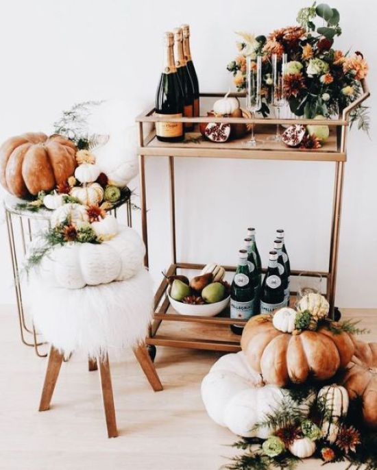 A Modern Thanksgiving Bar Cart With A Gilded Cart Fall Blooms Heirloom Pumpkins And Faux Fur