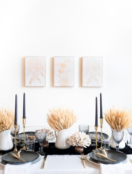 A Modern Thanksgiving Tablescape With A Black Runner Plates And Tall Candles Wheat Arrangements And Grey Glasses