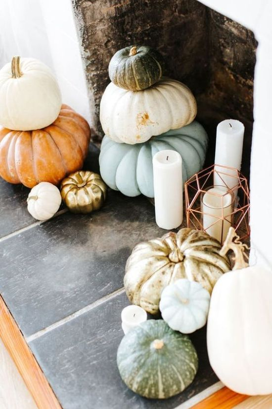 A Thanksgiving Fireplace With Stacked Heirloom Pumpkins And Pillar Candles In Lanterns And Without Them