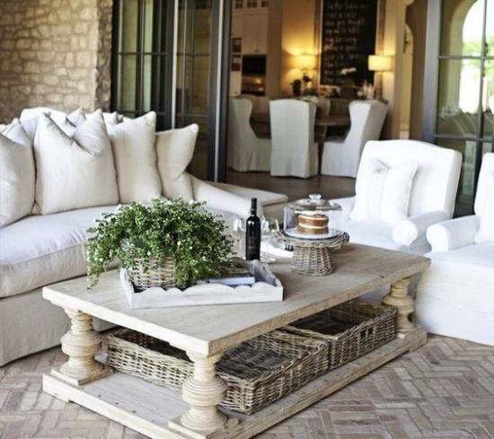 A Chic Farmhouse Coffee Table With Basket Trays Under It To Store Some Blankets And Pillows
