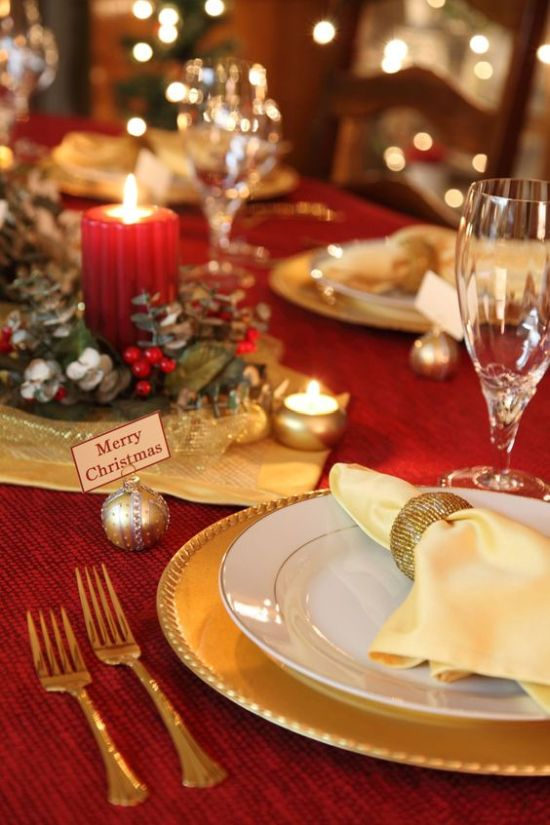 A Chic Red And Gold Christmas Table With A Greenery And Candle Centerpiece With Gold Chargers And Cutlery Plus Mini Candles And Ornaments