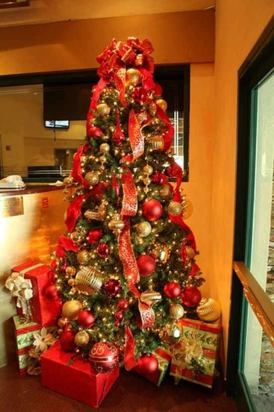 A Christmas Tree Decorated With Red And Gold Ornaments And Ribbons And Gift Boxes Plus Bows On Top