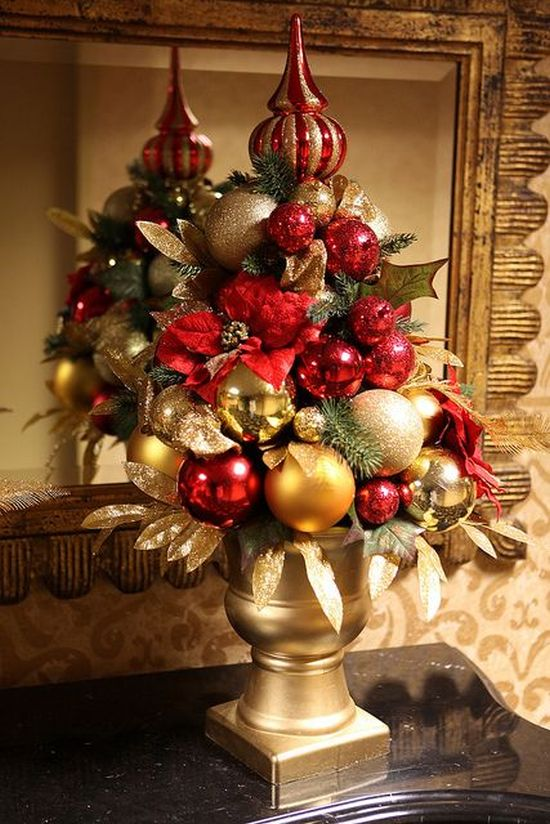 A Red And Gold Christmas Tree Composed Of Ornaments With Gilded Leaves And A Shiny Topper