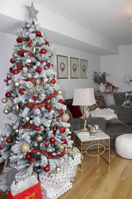 A Snowy Christmas Tree With Gold And Red Ornaments With Plaid Ribbons And A Silver Tree Topper