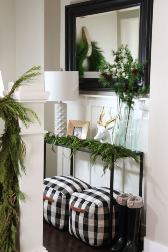 Farmhouse Entryway Christmas Decor With Evergreens And A Couple Of Buffalo Check Poufs