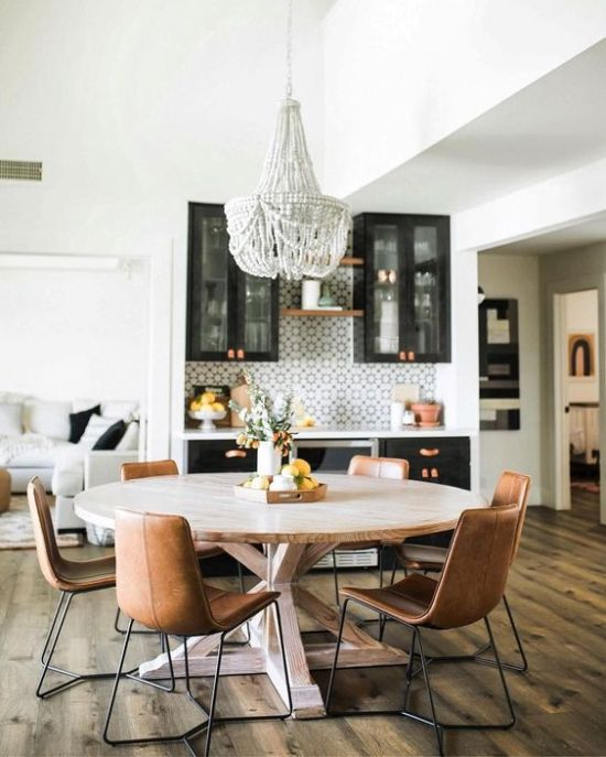 Dining Room Décor With A Round Wooden Table With Leather Chairs