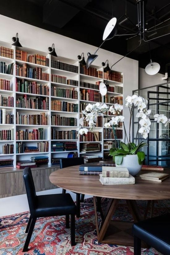 Home Library With A Large Round Table And Black Leather Chairs