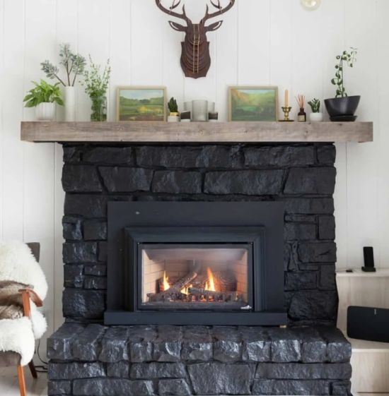 Large Black Stone Clad Fireplace With A Wooden Mantel