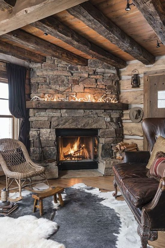 Stone Fireplace With Layered Rugs And Wicker And Leather Furniture