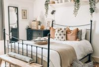 Boho Bedroom Decor With A Forged Bed And Potted Greenery