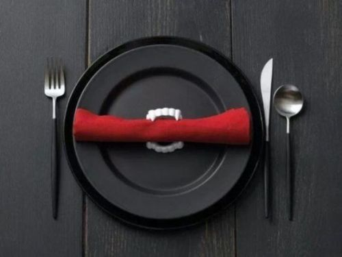 Black Cutlery And A Red Napkin With Vampire Teeth